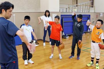 ペットボトルを使って正しい投球動作を学ぶ子どもたち=三菱重工総合体育館