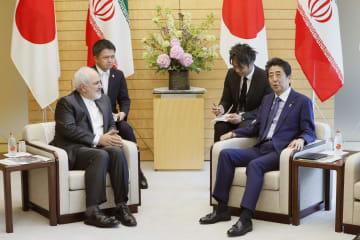イランのザリフ外相(左)と会談する安倍首相=16日午前、首相官邸