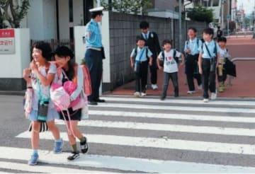 登校する児童に交通指導をする大分中央署員=16日午前7時35分、大分市碩田町