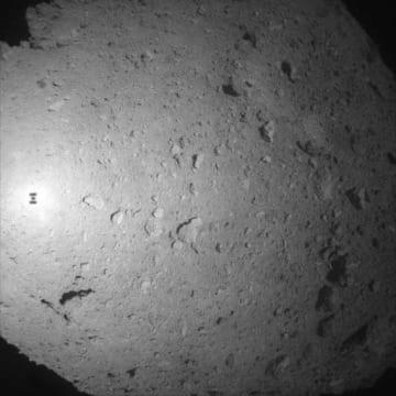 はやぶさ2が降下途中、小惑星りゅうぐうの上空60メートル付近で撮影した画像。はやぶさ2の影が左端中央に写っている(JAXA提供)