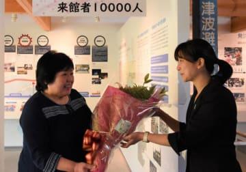 1万人目の来館者となり、花束を受け取る瀬川ハル子さん(左)