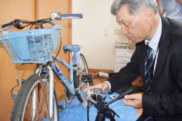 自転車の傷を写真撮影する佐々木尋貴さん=16日、熊谷市