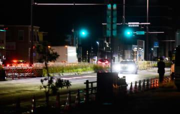 【事故現場の中央分離帯開口部付近で同系統の車種を使い検分に当たる捜査員ら=津市本町の国道23号で】