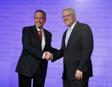 握手をするオーストラリアのモリソン首相(右)と、労働党のショーテン党首=8日、キャンベラ(ゲッティ=共同)