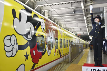 人気キャラクター「ミッキーマウス」の装飾を施し出発する九州新幹線。旅行かばんを手に走るイラストなどが描かれ、乗客らの目を楽しませていた=17日午後、JR博多駅