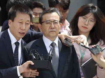 ソウル中央地裁前で記者に囲まれる金学義容疑者(中央)=16日(聯合=共同)