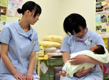 看護体験で新生児を抱く生徒