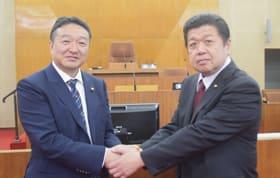 握手を交わし、円滑な議会運営を誓い合う工藤議長(左)と杉尾副議長