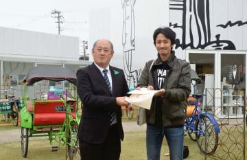 1万5千人目の入館者となった福地正太郎さん(右)