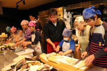庄司さん(中央)の指導でタケノコを切り、料理を作る子どもたち=伊勢原市内の創作和食料理店「天Sora」