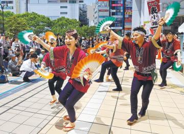 軽やかに舞い、観客を魅了するすずめ踊りの踊り手たち=18日午前11時ごろ、仙台市青葉区のJR仙台駅西口