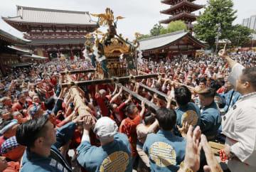 浅草神社の三社祭で、威勢のいい掛け声とともにみこしを担ぐ人たち=18日、東京都台東区