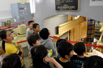大きな音を立て回転する水車軸を見学する児童ら