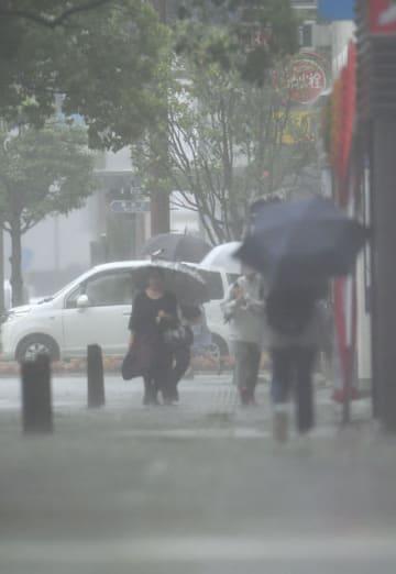 大雨で視界が悪い中、傘を差し慎重に歩く市民ら=18日午前、宮崎市高千穂通1丁目