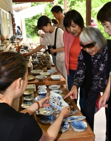 陶芸家と会話しながら買い物を楽しむ来場者=相模原市緑区の陶釉舎