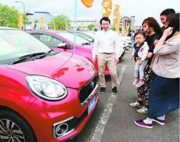 担当者(左端)から中古車の説明を受ける来場者=徳島市のマリンピア沖洲特設会場