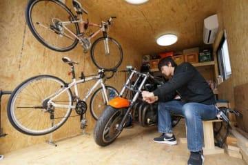小屋でバイクを整備する三好さん