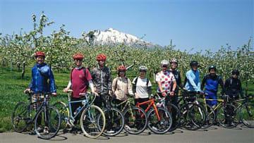 岩木山とリンゴの花をバックに記念写真に納まる参加者ら(北野さん提供)