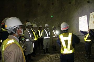 掘削現場で説明を受ける国会議員ら=久山トンネル内
