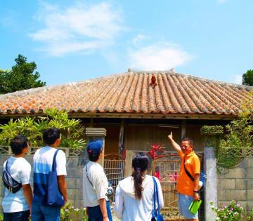 大宜味村喜如嘉の古民家を観光客に案内するオクマプライベートビーチ&リゾートの大山章さん(右)=同ホテル提供