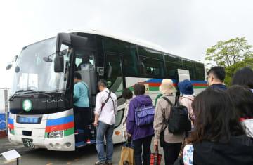 箱根ロープウェイが全線運休となったため、早雲山駅で代行バスに乗る観光客=19日午前9時35分ごろ