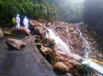 大雨の影響で岩や土砂が流れ込んだ鹿児島県屋久島町の県道=19日午前(鹿児島県屋久島事務所提供)