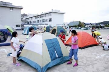 校庭にテントを張る子どもたち。3年目は地区外の人を含め約180人が参加した=2018年8月25日、福井県福井市社南小