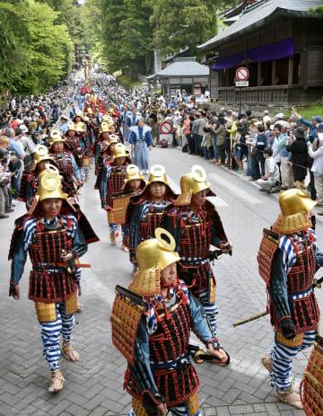 見物客がカメラを向ける中、参道を堂々と練り歩く鎧武者ら=18日午前11時35分、日光市山内