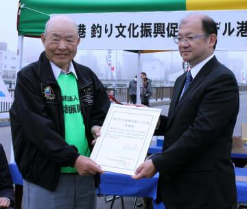 酒井港湾空港部長から指定証を受け取った高橋会長(左)