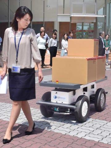 人の後を追従する運搬ロボットを体験する立命館大職員ら(滋賀県草津市、立命館大びわこ・くさつキャンパス)