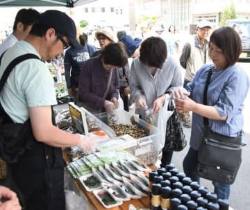 新鮮な野菜や海産物が並ぶ会場で買い物を楽しむ来場者