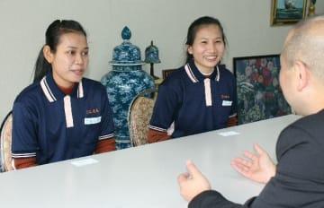 説明を聞くカンボジア人のテェム・テイリーさん(中央)とナック・ヴァンナーさん(左)=日田市石井