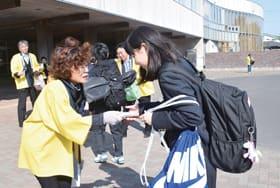 生徒たちに啓発品を配り、詐欺などの注意を喚起する会員たち