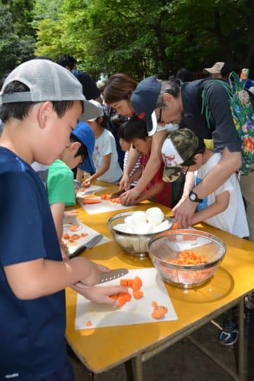 屋外でカレーの調理に取り組む参加者ら=川崎市麻生区の市黒川青少年野外活動センター