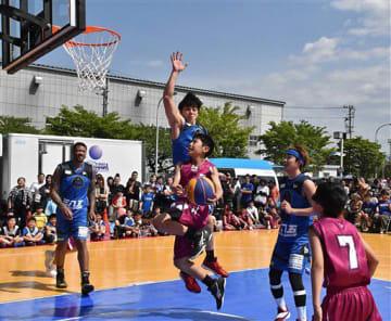 小学生チームとエキシビションマッチを行う八戸ダイムの選手(青)