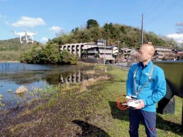 ドローンで深泥池のシカ害を調査している丹羽准教授。例年は左側の岸辺にミツガシワが白い花を咲かせるが、今年はシカに食べられてしまっていた(京都市北区)