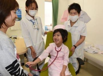 聴診器を手に医師気分を味わう子ども