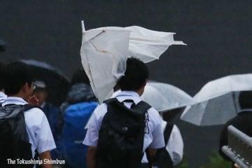 傘が壊れるほどの強い雨と風になった=午後6時ごろ、JR徳島駅前