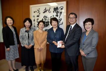 寄付金を手渡す葉月会の高森会長(右から3人目)=20日午前、宮崎市・宮崎大木花キャンパス