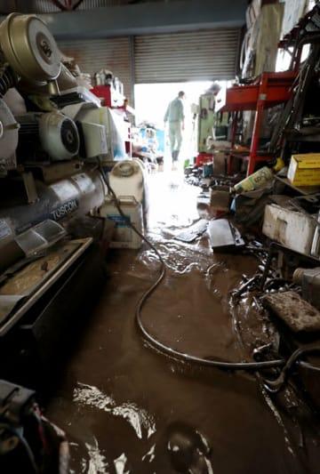 大雨による増水で泥水が流れ込んだ自動車整備工場=20日午前、串間市市木
