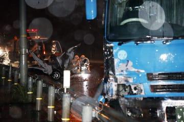 右前部が壊れた大型トラック(手前)と大破した軽トラック(中央)=20日午後9時40分頃、三好市山城町下川
