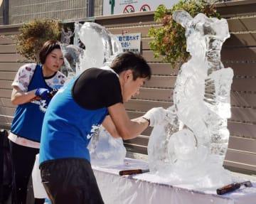 のこぎりやのみを使い、氷柱から繊細な彫刻作品を削り出す出場者=柏市