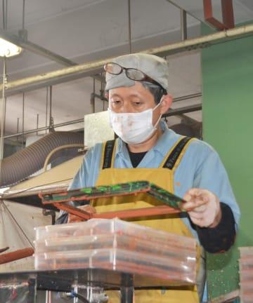 真剣な表情で成形作業をする本田さん=川崎市高津区の日本理化学工業