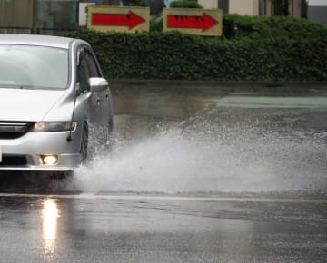 水しぶきを上げながら、冠水した道路を走る車=21日午前9時5分ごろ、横浜駅西口