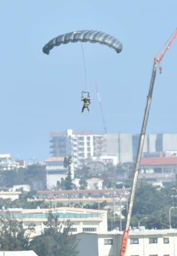 パラシュート訓練で米軍嘉手納基地内(沖縄県)に降下する米兵=21日午後3時37分、嘉手納町役場屋上から