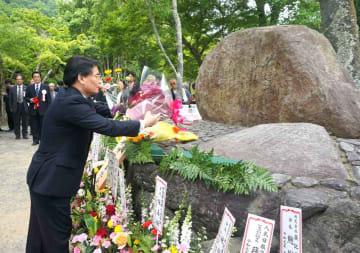 周恩来元首相の詩句「雨中嵐山」を刻んだ碑に花を手向ける関係者たち(京都市右京区・亀山公園)