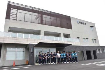 新富町上富田に開院した「川原眼科」の前で笑顔を見せるスタッフら