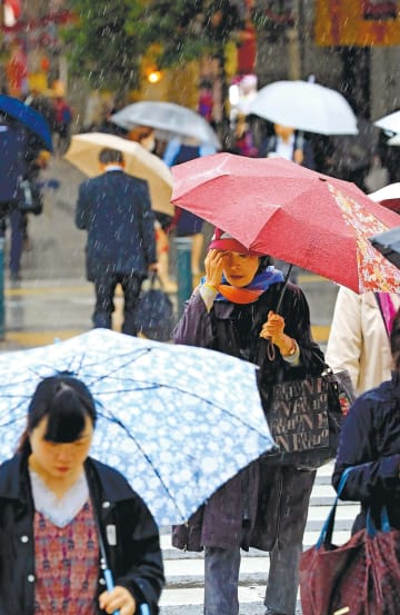 降りしきる雨の中、傘を差しながら歩く人々=21日午前9時40分ごろ、仙台市青葉区の東二番丁通