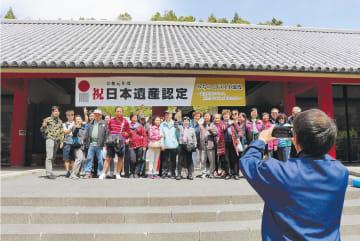 日本遺産認定を祝う看板の前で記念写真を撮る香港のツアー客=20日、宮城県涌谷町