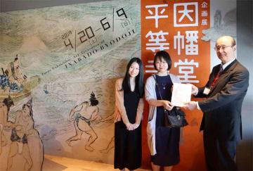 記念品を受け取る博さん(中央)と蒋さん(左)=京都市下京区・龍谷ミュージアム